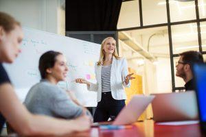 Une jeune femme d'affaires fait une présentation sur ses projets d'avenir à ses collègues au bureau.