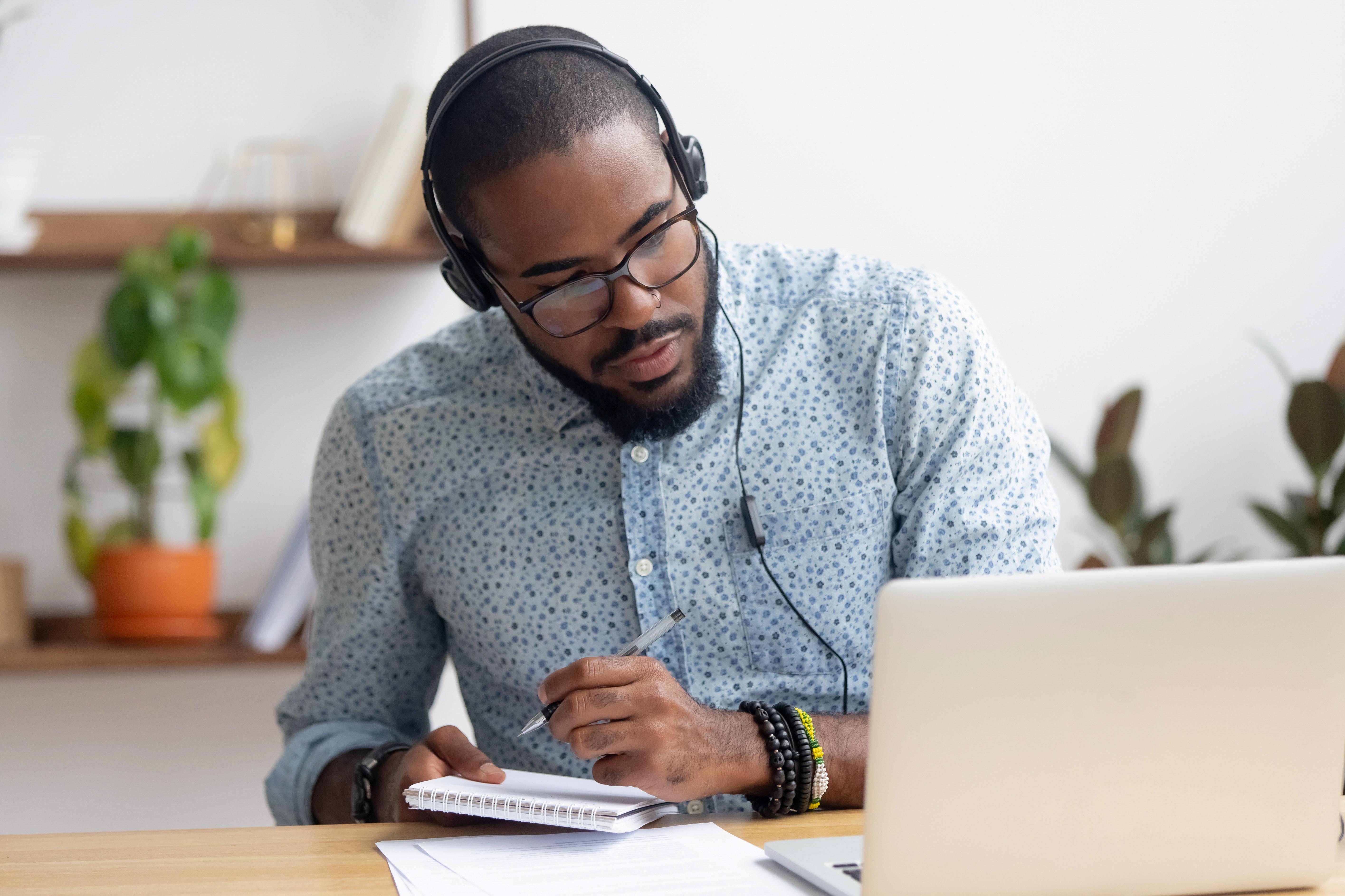 focused-african-businessman-in-headphones-writing-notes-watching-webinar