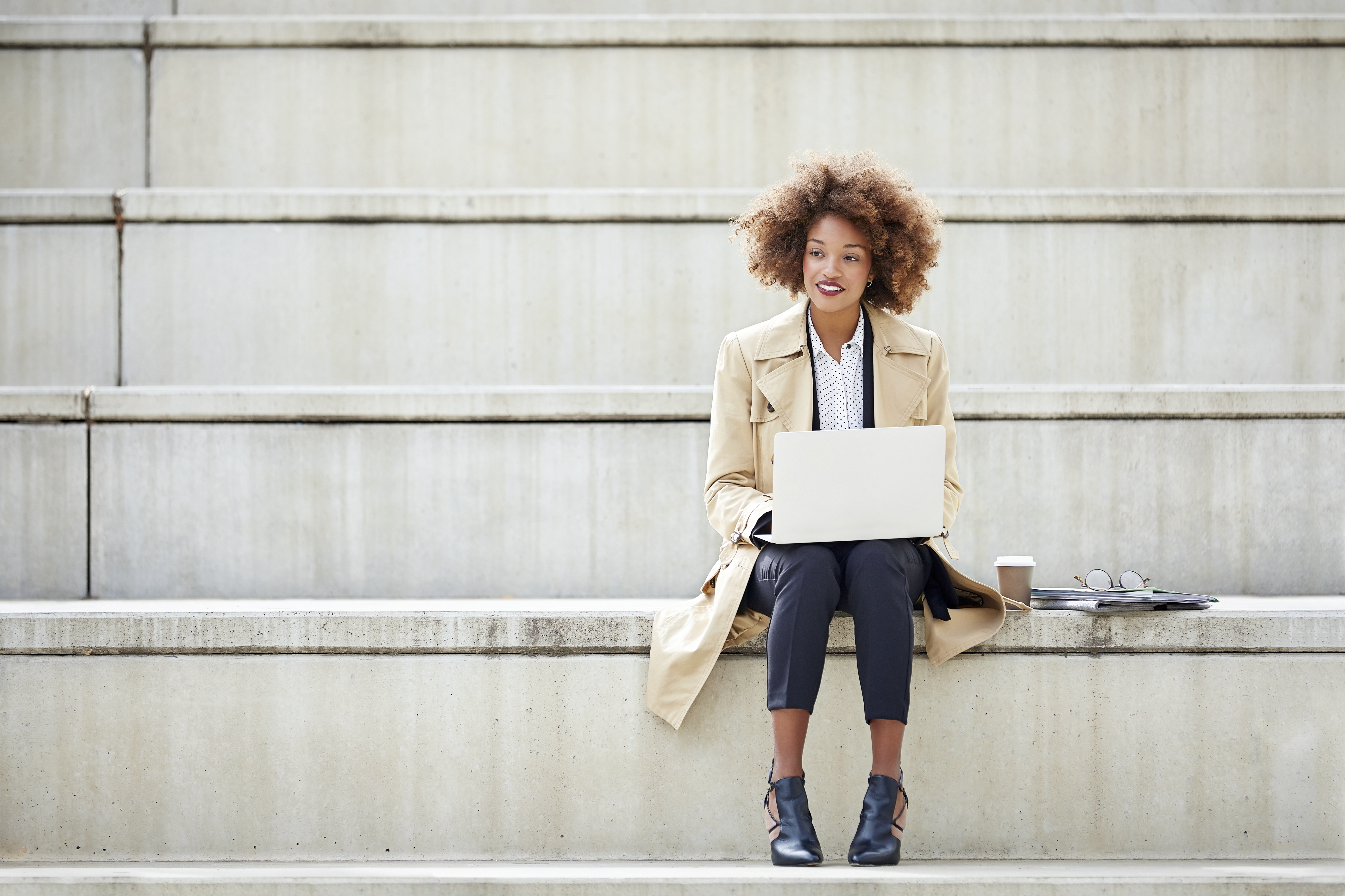 thoughtful-businesswoman-with-laptop-on-steps